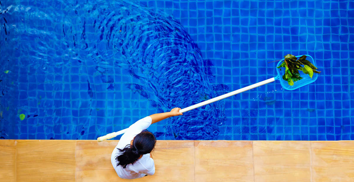 person from pool maintenance company skimming the water of a pool