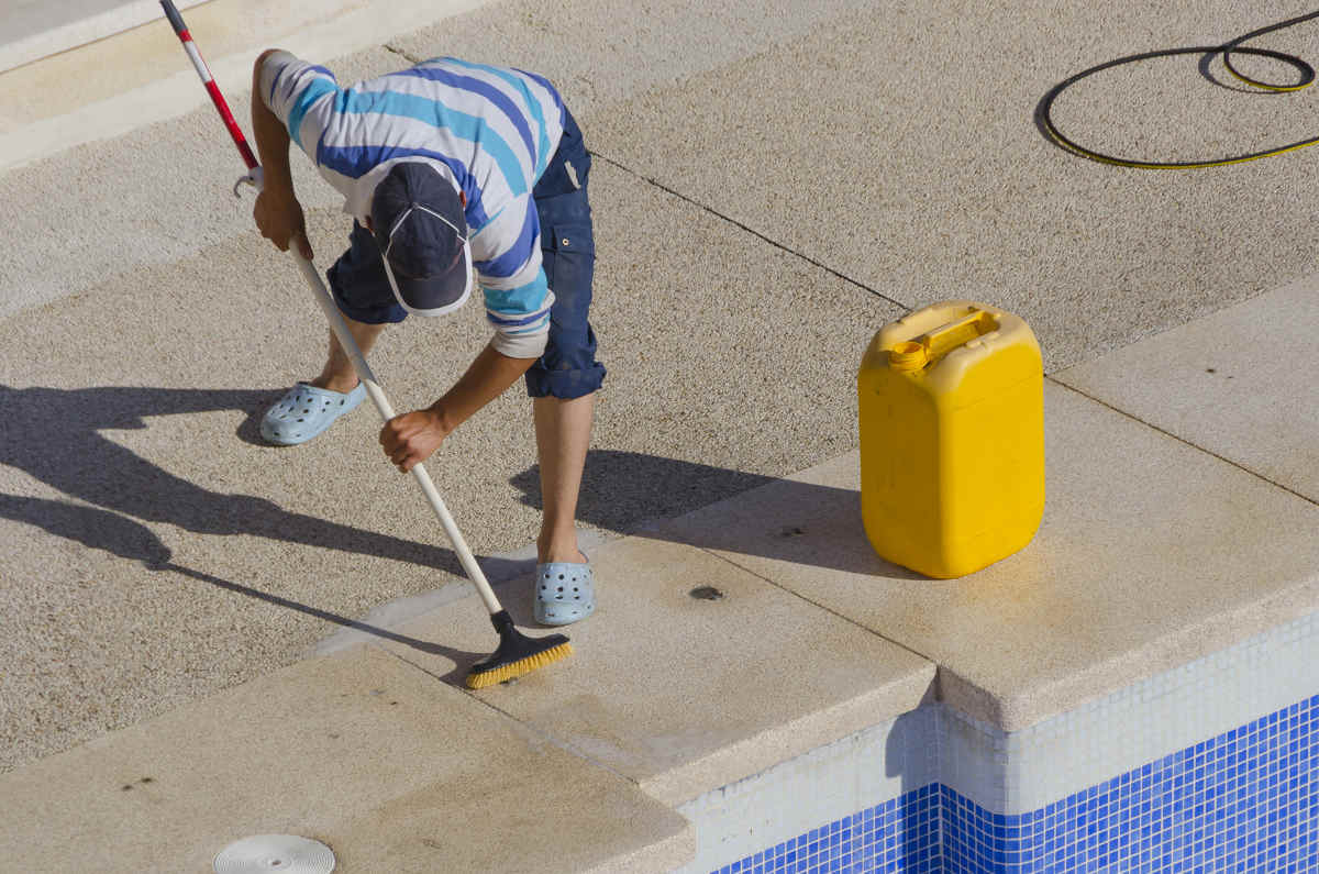 an experienced pool maintenance worker scrubbing the surfaces around the pool